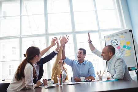 editors: Photo editors giving high-five in meeting room at creative office