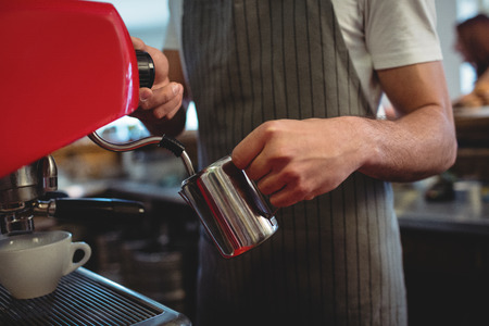 coffee house: Midsection of male barista using espresso maker at coffee house