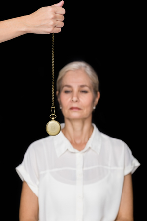 hypnotize: Cropped image of hypnotherapist holding pendulum before woman against black background