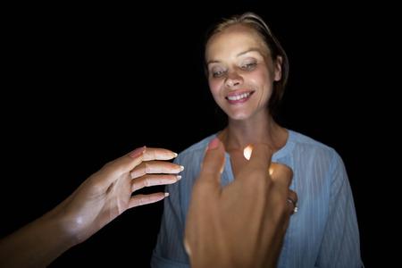hypnotist: Cropped image of hypnotist hypnotizing woman against black background