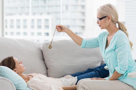 Hypnotherapist hält Pendel von Patienten auf dem Sofa zu Hause
