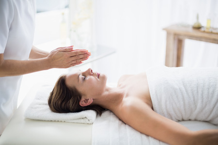 reiki: Midsection of therapist performing reiki on woman at spa Stock Photo