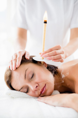 Masseur giving ear candle treament to young woman at spa