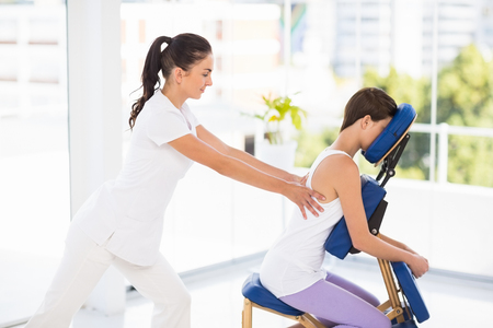 masseuse: Woman being massaged on chair by masseuse at spa