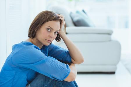 desolaci�n: Portrait of sad young woman sitting by sofa at home Foto de archivo