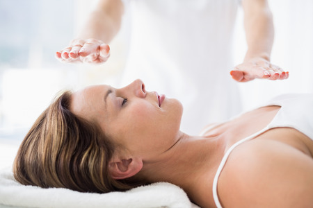 reiki: Midsection of therapist performing reiki treatment on woman at spa