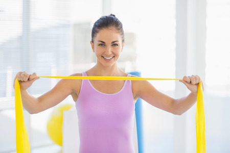resistance: Portrait of smiling woman holding resistance band at fitness studio