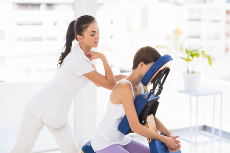 massage chair: Masseuse giving back massage to woman on chair at spa Stock Photo