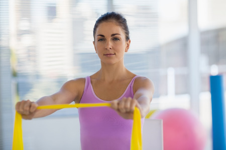 resistance: Portrait of woman holding resistance band at fitness studio Stock Photo