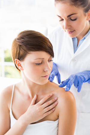 doctor examining woman: Doctor examining woman back at clinic