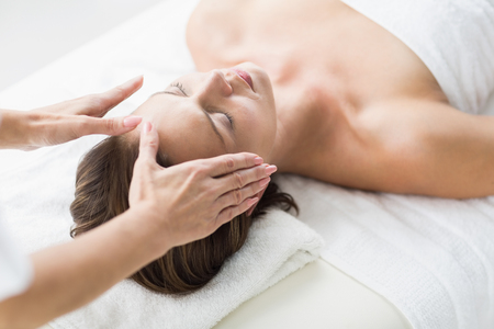 reiki: Cropped hands of therapist performing reiki on woman at spa Stock Photo