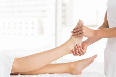 masseur: Midsection of masseur giving foot massage to woman at spa