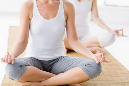 health club: Women in lotus position doing yoga at health club Stock Photo