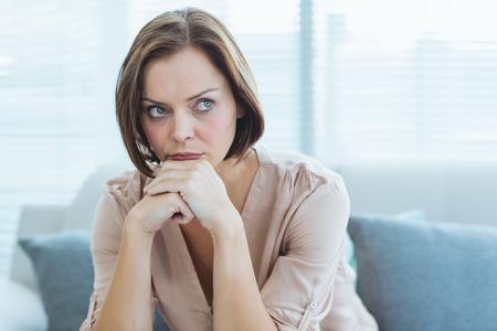 desolaci�n: Sad joven sentado en el sof� en casa