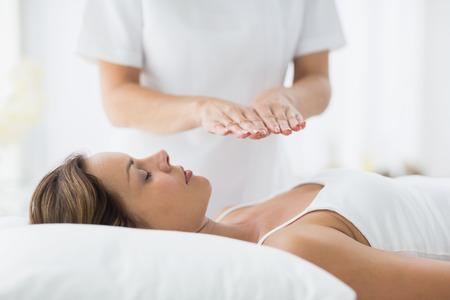reiki: Young woman receiving reiki treatment at spa
