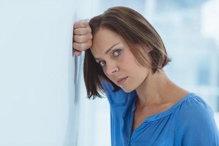 desolaci�n: Portrait of sad woman standing by wall at home Foto de archivo