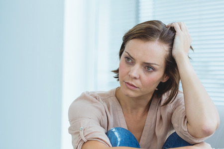 Depressed woman looking away at home Stock Photo