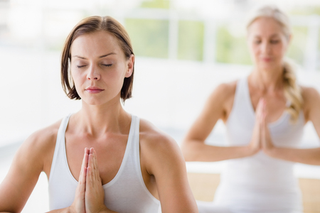 closed club: Women with eyes closed doing yoga at health club