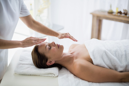 reiki: Midsection of therapist performing reiki on young woman at spa Stock Photo