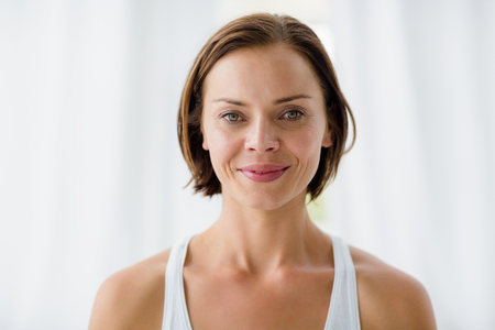 middleaged: Portrait of smiling young woman standing in fitness studi