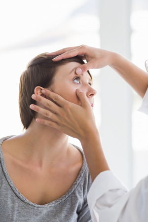 eye service: Cropped image of doctor checking woman eye at clinic Stock Photo