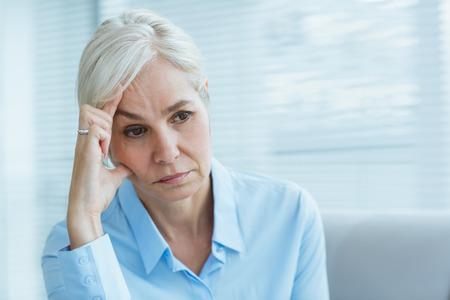 dreariness: Sad senior woman looking away at home