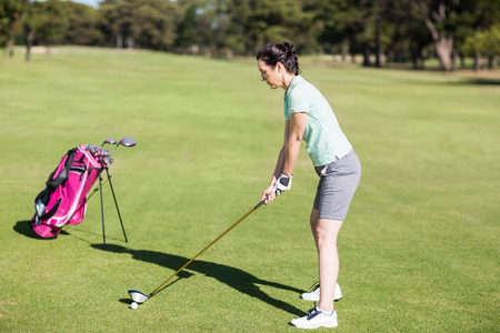 woman golf: Side view of woman playing golf while bending on field
