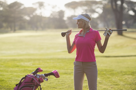 woman golf: Confident mature woman carrying golf club while standing on field