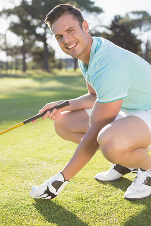 by placing: Portrait of confident golfer man placing golf ball on tee while crouching at field Stock Photo