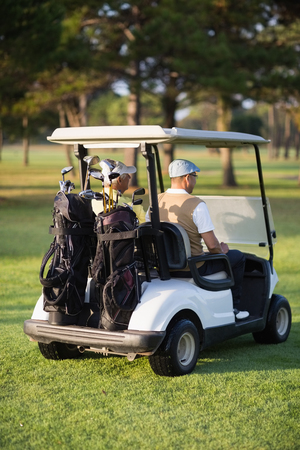 senior men: Rear view of male golfer friends sitting in golf buggy on sunny day