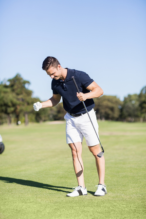 clenching fists: Golfer clenching fists while standing on golf course