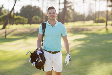 golf bag: Portrait of smiling young man carrying golf bag while standing on field
