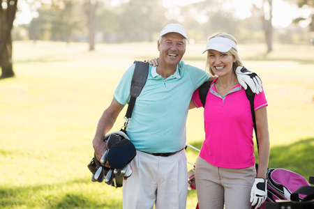 arm around: Happy mature golfer couple with arm around while standing on field