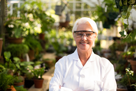 protective eyewear: Portrait of confident female scientist wearing protective eyewear at greenhouse