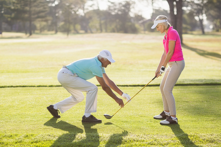 woman golf: Side view of mature male teaching woman to play golf