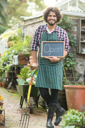 western script: Portrait of male gardener with open sign holding gardening fork outside greenhouse Stock Photo