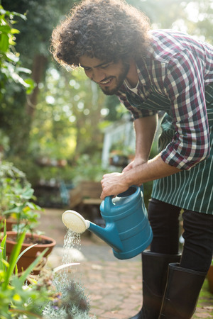regando plantas: Varón feliz jardinero de las plantas de riego del invernadero fuera