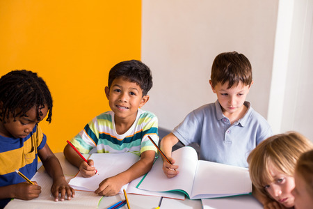 classmates: Portrait of cute boy with classmates in classroom Stock Photo