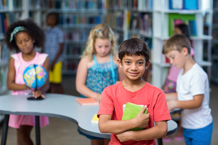 classmates: Portrait of boy holding books against classmates in library