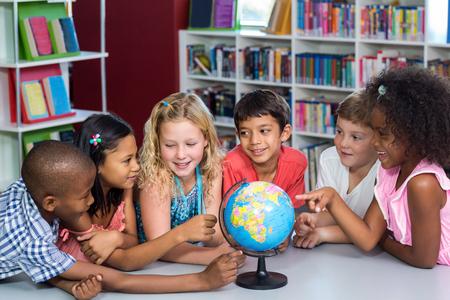 adolescentes estudiando: Niños sonrientes con el globo sobre la mesa en la biblioteca