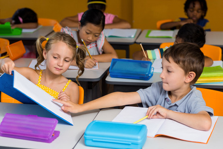 showed: Cute boy pointing at book showed by classmate in classroom
