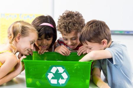 niños reciclando: Los niños lindos mirando botellas de plástico en la caja de reciclaje en el aula