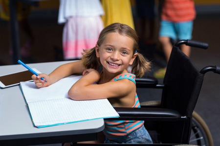 Little girl in wheelchair in classroom at school Stock Photo