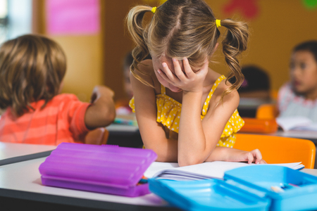 covering the face: Frustrated girl with hand covering face in classroom