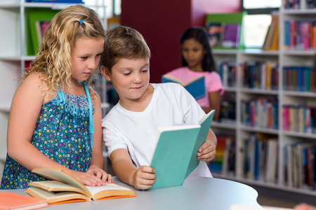 classmate: Cute boy showing book to female classmate in library
