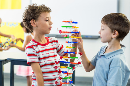 observing: Boys observing at DNA model in classroom Stock Photo