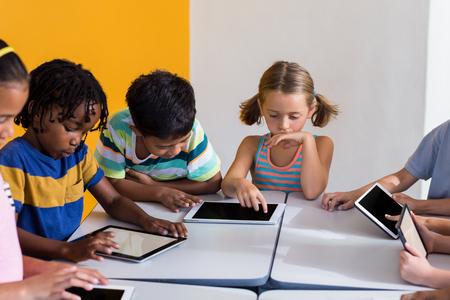 multi ethnic children: Multi ethnic children using digital tablets in classroom
