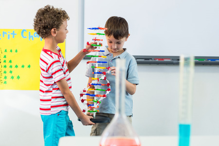 schoolboys: Cute schoolboys holding DNA model in classroom