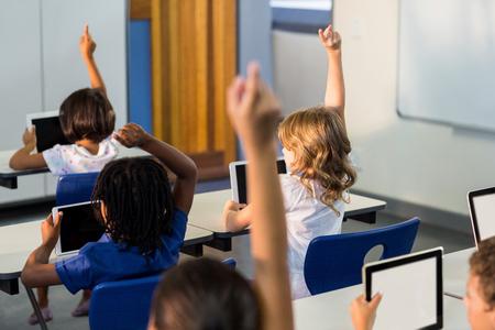 Hintere Ansicht von Kindern mit den digitalen Tabletten, die ihre Hände im Klassenzimmer anheben