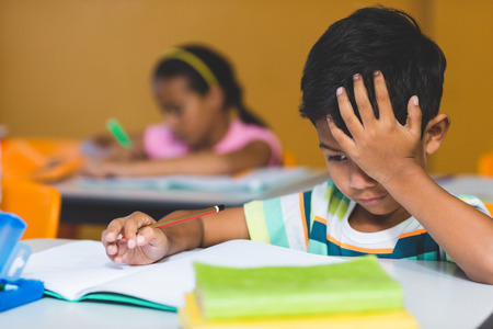 irritated: Irritated boy with head in hand looking at book on bench in classroom